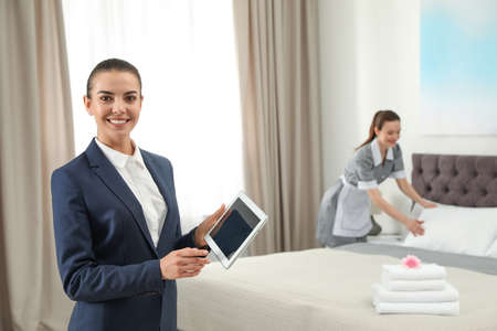 Photo for Housekeeping manager with tablet checking maid work in hotel room. Space for text - Royalty Free Image