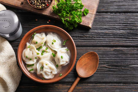 Photo for Bowl of tasty dumplings served on wooden table, flat lay. Space for text - Royalty Free Image