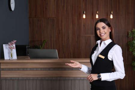 Photo pour Portrait of receptionist at desk in lobby - image libre de droit