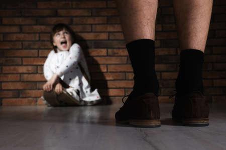 Foto de Adult man without pants standing in front of scared little girl indoors. Child in danger - Imagen libre de derechos