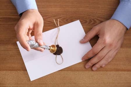 Photo pour Male notary sealing document at wooden table, top view - image libre de droit