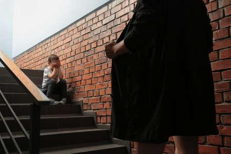 Foto de Male exhibitionist opening his coat in front of scared little boy indoors. Child in danger - Imagen libre de derechos