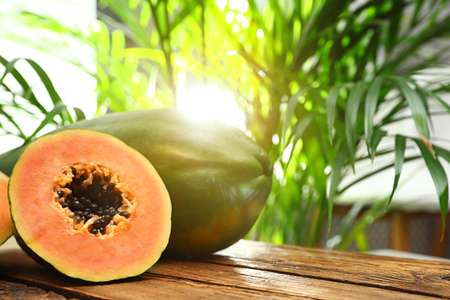 Photo for Fresh juicy ripe papayas on wooden table against blurred background, closeup view. Space for text - Royalty Free Image