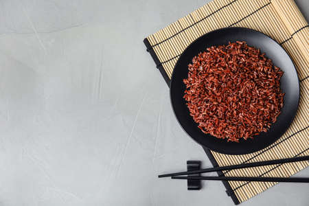 Foto de Flat lay composition with delicious cooked brown rice on grey table. Space for text - Imagen libre de derechos