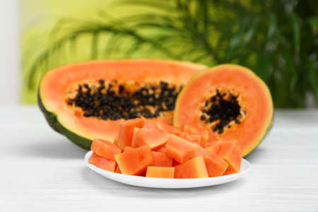 Photo for Fresh juicy papayas on white table against blurred background - Royalty Free Image