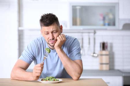 Photo pour Portrait of unhappy man eating broccoli salad in kitchen - image libre de droit