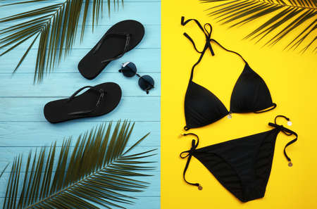 Photo for Black swimsuit, flip flops, sunglasses and tropical palm leaves on color background, flat lay - Royalty Free Image