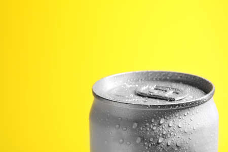 Foto de Aluminum can of beverage covered with water drops on yellow background, closeup. Space for text - Imagen libre de derechos