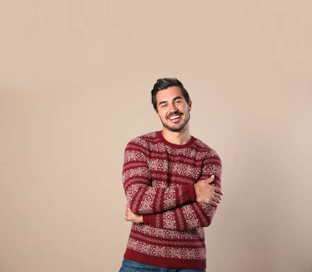 Photo pour Portrait of happy man in Christmas sweater on beige background - image libre de droit