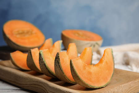 Photo for Slices of ripe cantaloupe melon in wooden tray on table - Royalty Free Image
