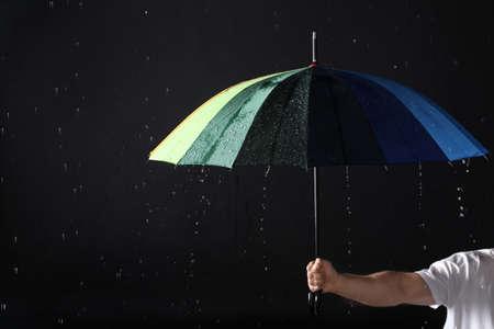 Foto de Man holding color umbrella under rain against black background, closeup - Imagen libre de derechos