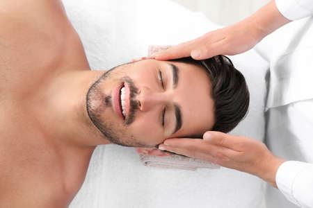 Photo for Handsome young man receiving face massage on spa table, top view - Royalty Free Image