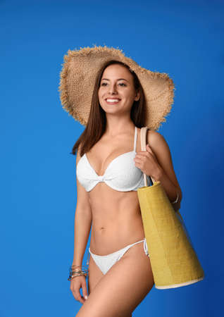 Photo for Pretty sexy woman with slim body in stylish  white bikini on blue background - Royalty Free Image