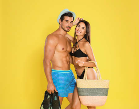 Photo for Young attractive couple in beachwear with flippers and bag on yellow background - Royalty Free Image