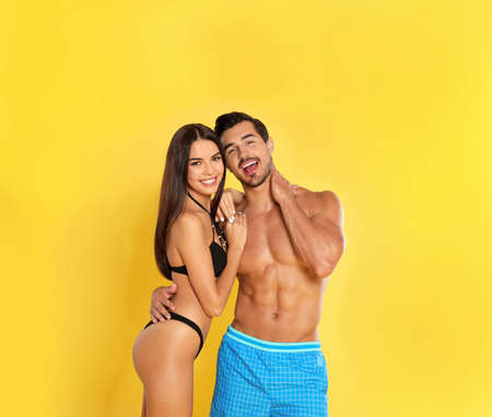 Photo for Young attractive couple in beachwear on yellow background - Royalty Free Image