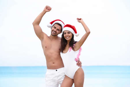 Photo for Happy young couple with Santa hats together on beach - Royalty Free Image