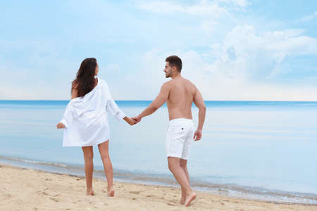 Photo for Happy young couple walking together on beach near sea - Royalty Free Image