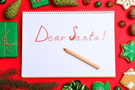Foto per Notebook with words DEAR SANTA and Christmas decorations on red background, flat lay - Immagine Royalty Free