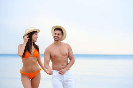 Photo for Happy young couple walking together on beach - Royalty Free Image
