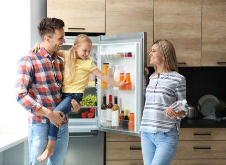 Foto de Happy family with bottle of water near refrigerator in kitchen - Imagen libre de derechos