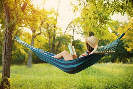 Foto de Young woman reading book in comfortable hammock at green garden - Imagen libre de derechos