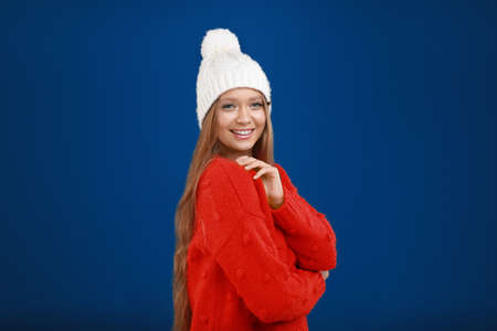 Photo pour Young woman in warm sweater and hat on blue background. Winter season - image libre de droit