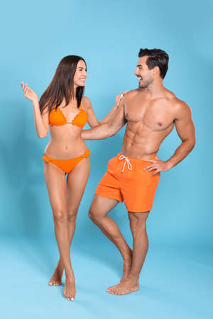 Photo for Young attractive couple in beachwear on blue background - Royalty Free Image