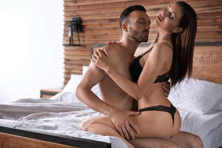 Photo pour Passionate young couple having sex in bed at home - image libre de droit