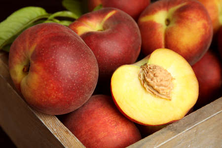 Photo pour Tasty peaches and leaves in wooden crate, closeup - image libre de droit