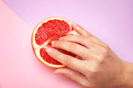 Photo pour Young woman touching half of grapefruit on color background, above view. Sex concept - image libre de droit