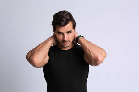 Photo pour Portrait of handsome young man in black t-shirt on grey background - image libre de droit