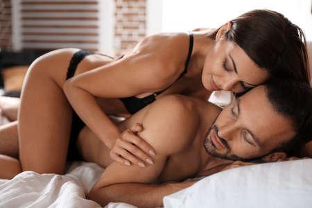 Foto de Passionate young couple having sex in bed at home - Imagen libre de derechos