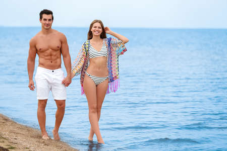 Photo for Happy young couple walking together on sea beach. Space for text - Royalty Free Image