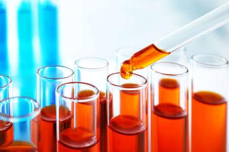 Foto de Dropping sample into test tube with orange liquid, closeup - Imagen libre de derechos