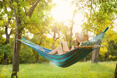 Photo pour Young woman reading book in comfortable hammock at green garden - image libre de droit