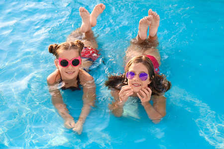 Foto de Happy cute girls in swimming pool on sunny day - Imagen libre de derechos