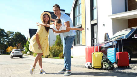 Foto de Happy family with suitcases near house outdoors. Moving day - Imagen libre de derechos