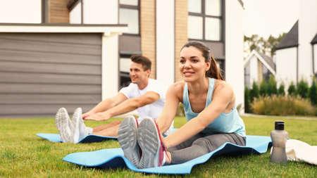 Photo pour Sporty couple practicing morning yoga at backyard. Healthy lifestyle - image libre de droit
