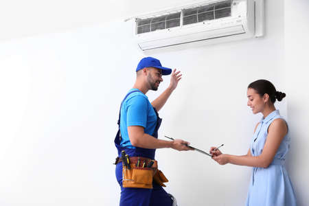 Photo for Professional technician speaking with woman about air conditioner indoors - Royalty Free Image