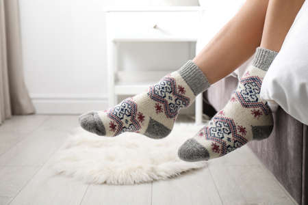 Photo pour Woman wearing knitted socks on bed indoors, closeup. Warm clothes - image libre de droit