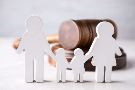 Foto de Figure in shape of people and wooden gavel on light table. Family law concept - Imagen libre de derechos
