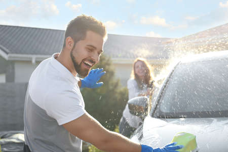Photo pour Happy couple washing car and having fun at backyard on sunny day - image libre de droit