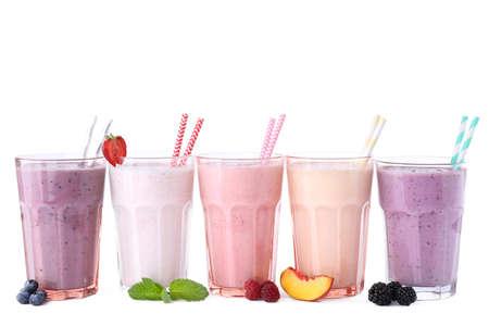 Foto de Different fresh tasty milk shakes in glasses with ingredients on white background - Imagen libre de derechos