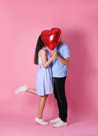 Foto de Lovely couple hiding behind heart shaped balloon on pink background. Valentine's day celebration - Imagen libre de derechos