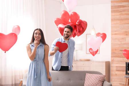 Foto de Lovely couple with heart shaped balloons in living room. Valentine's day celebration - Imagen libre de derechos