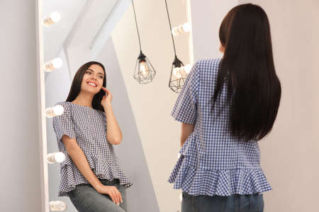 Photo pour Young attractive woman looking at herself in stylish mirror at home - image libre de droit