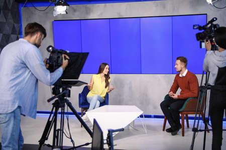 Foto de Presenters and video camera operator working in studio. News broadcasting - Imagen libre de derechos