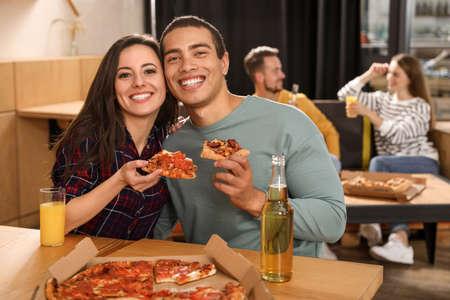 Foto de Young couple eating delicious pizza in cafe - Imagen libre de derechos