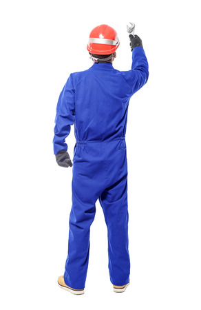 Foto de A back view of a worker holding a wrench isolated on white background. - Imagen libre de derechos