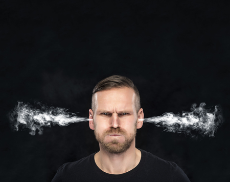 Foto de Angry man with smoke or fume coming out from his ears on dark background. - Imagen libre de derechos